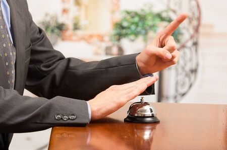hospitality staff: hand of businessman customer ringing hotel bell in reception desk close up selective focus