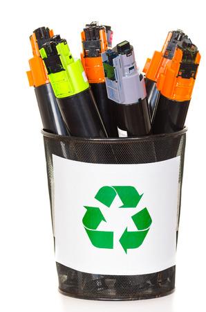 Kopieermachine cartridges te recyclen in een emmer op wit wordt geïsoleerd