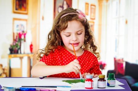 niños pintando: niña con la pintura del cepillo rizada hermosa
