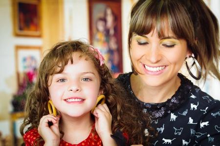 aretes: Retrato de la hermosa madre e hija jugando con pendientes