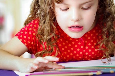 Cute little girl doing her homework coloring Stock Photo