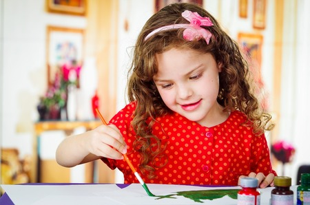 Happy little artistic girl painting on paper
