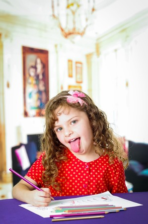 imaginative: Adorable preschooler girl drawing and coloring, putting her tongue out Stock Photo