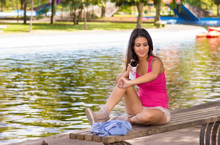 Young beautiful brunette girl sitting next to a lagoon spraying insect repellent