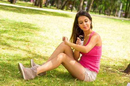 woman resting: Brunette model wearing pink top and white shorts sitting on grass in park playing with mobile phone.