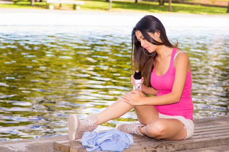 insect: Brunette model wearing pink top and white shorts relaxing in park environment, sitting on bench next to lake using insect repellent spray.