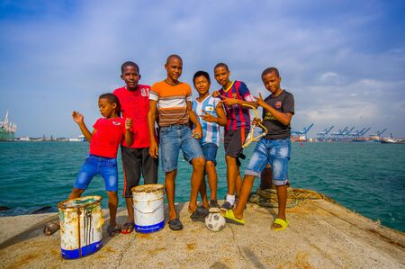 COLON, PANAMA - APRIL 15, 2015: local teens hanging by the harbor where they fish and play football in the port of Colon in Panama. Editorial