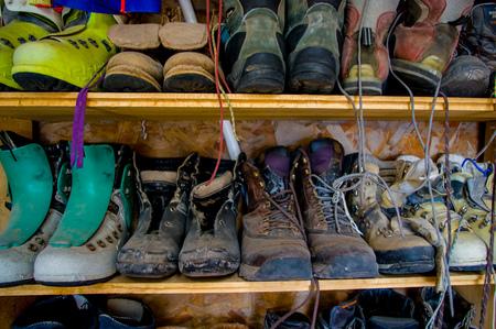 shoe shelf: climbing hiking used boots in an outdoor shoe shelf