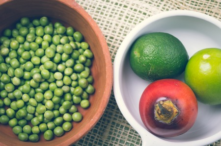 tomate de arbol: tazón de cerámica terracota con guisantes crudos junto a la placa blanca de tomate fresco árbol orgánica y limas.