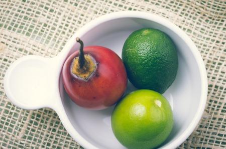 tomate de arbol: Aromático tomate de árbol del jardín-fresco y limas en un tazón blanco.