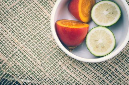 tomate de arbol: Tomate de árbol y limas cortadas en mitades dentro de un recipiente blanco con fondo de cáñamo rústico.