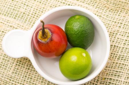 tomate de arbol: Tomate de árbol aromático y el jardín-fresco y limas en un tazón blanco y fondo rústico Foto de archivo