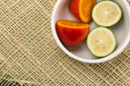 tomate de arbol: Tomate de árbol y limas cortadas en mitades dentro de un recipiente blanco con fondo de cáñamo rústico Foto de archivo