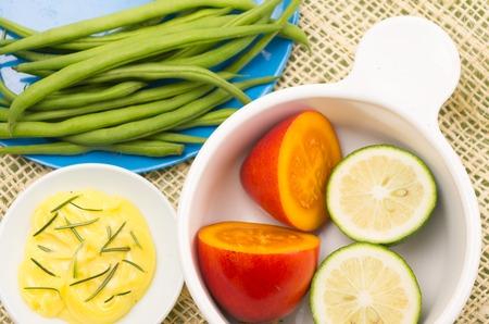 tomate de arbol: Platos de colores brillantes con judías verdes, la mantequilla y el cuenco con tomate de árbol, más limas.