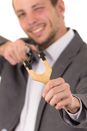 buisness: Handsome buisness man smiling concentrated aiming a slingshot isolated over white background.
