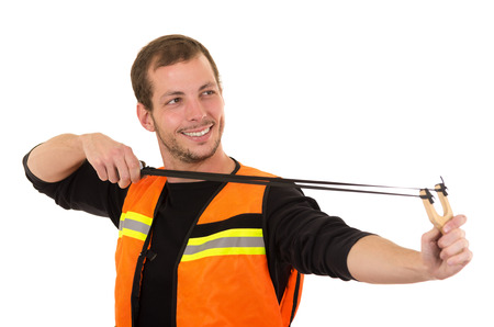 vest in isolated: Handsome man concentrated aiming a slingshot with security vest isolated over white background.