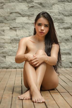 desnudo: Modelo de latina sexy sentado desnudo en el piso de madera frente a la c�mara con las piernas y los brazos cruzados encubrir art�sticamente delante de la pared de ladrillo gris. Foto de archivo
