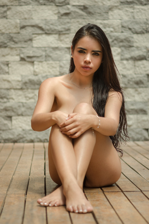 Sexy latina model sitting naked on wooden floor facing camera with legs and arms crossed covering up artistically in front of grey brick wall. Stock Photo