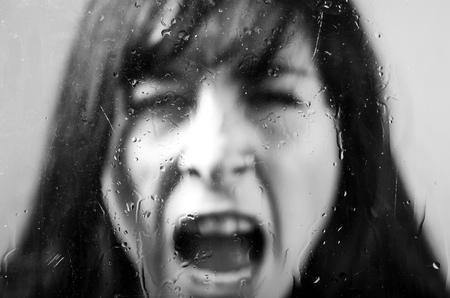 melancholy: Black and white closeup portrait of brunette girl behind glass screaming concept of melancholy, sadness, loneliness Stock Photo
