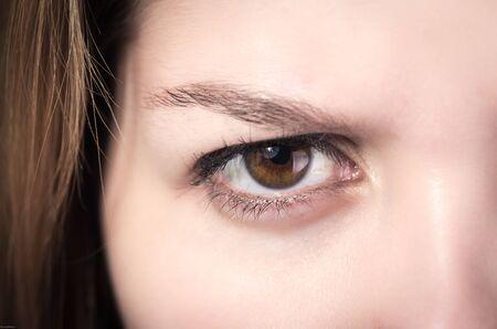 brown eye: Closeup of young girls brown eye expressing anger