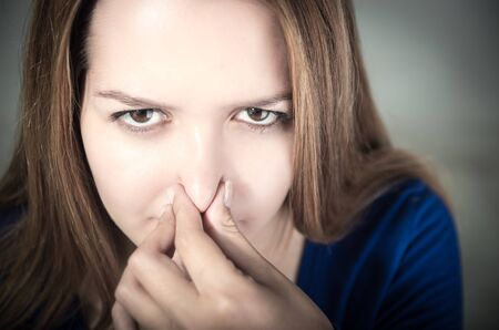 pinching: closeup portrait of young beautiful teen girls face pinching her nose Stock Photo