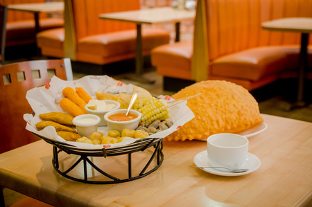 traditionally american: Mixed platter beautifully arranged with mix of typical latin foods such as empanadas, corn, abbas, salsas on table and large empanada next to basket. Stock Photo
