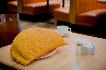 traditionally american: Large empanada and white coffee cup sitting on restaurant table with salt pepper visible.