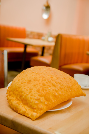 restaurant setting: Beautiful large yellow colored empanada sitting on small white plate in restaurant setting.