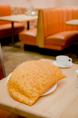 Beautiful large yellow colored empanada sitting on small white plate in restaurant setting.