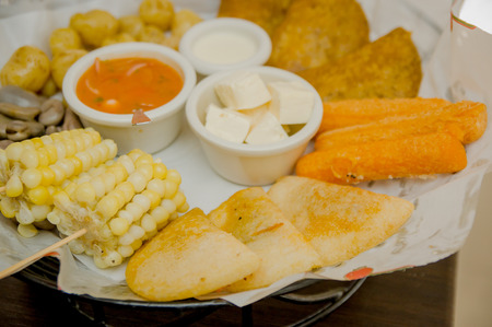 Closeup delicious food platter of typical latin foods such as corn, empanadas, abbas, cheese and salsas nicely arranged.