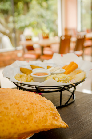 traditionally american: Large empanada on wooden table next to basket of typical latin foods, refreshing restaurant setting. Stock Photo