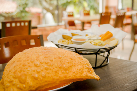 colombian food: Large empanada on wooden table next to basket of typical latin foods, refreshing restaurant setting. Stock Photo