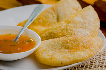 traditionally american: Three empanadas nicely arranged on white platter next to small salsa bowl and rustic background .
