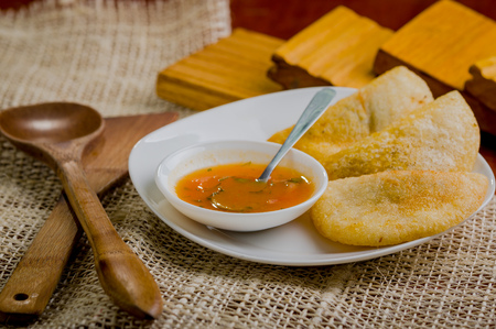 colombian food: Three empanadas nicely arranged on white platter next to small salsa bowl and rustic background .