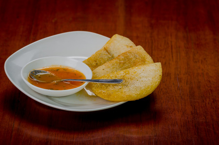 colombian food: White plate with three delicious empanadas lined up and small bowl of red salsa on top.