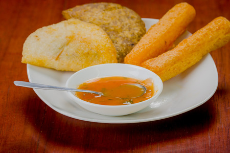 traditionally american: Mixed white plate of typical latin food including empanadas and a salsa bowl. Stock Photo