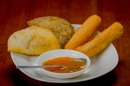 latin food: Mixed white plate of typical latin food including empanadas and a salsa bowl. Stock Photo