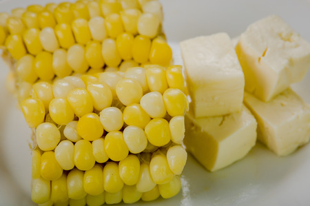 traditionally american: Cloeeup above angle of two halfs corn lying on white plate next to stable fresh cheese.