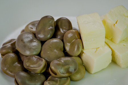 traditionally american: Closeup pile of cooked abbas next to small stable square pieces cheese on white surface.
