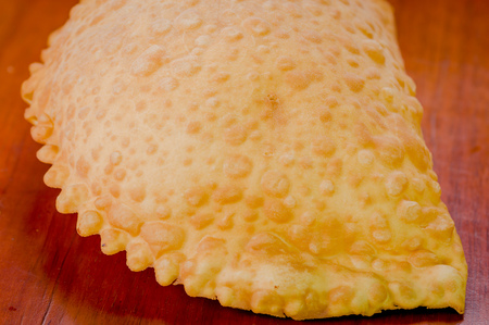 traditionally american: Large fluffy empanada beautiful color lying on wooden surface.
