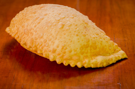 colombian food: Large fluffy empanada beautiful color lying on wooden surface.