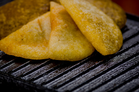 traditionally american: Closeup five empanadas lying in fan formation on black metal grill tablet. Stock Photo