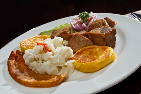 Fritada, carne de cerdo frito servido con tortillas de patatas, comida típica ecuatoriana