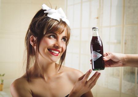 cola bottle: QUITO, ECUADOR - JULY 31, 2015: Beautiful retro girl receiving an old vintage coca cola bottle Editorial