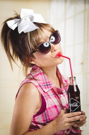 playfulness: QUITO, ECUADOR - JULY 31, 2015: Beautiful retro girl with sunglasses drinking from an old vintage coca cola bottle