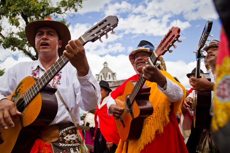 andean: PICHINCHA, ECUADOR - JUNE 30, 2011: Unidentified musicians playing guitar in parade at Inti Raymi indigenous celebration in Cayambe, Ecuador