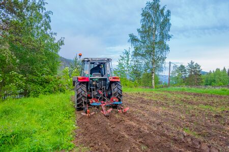 shot from behind: OSLO, NORWAY - 8 JULY, 2015: Tractor working in field opening preparing soil for planting vegetables, shot from behind angle.