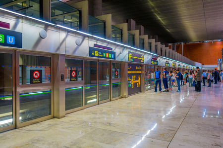 barajas: MADRID, SPAIN - 8 AUGUST, 2015: Train station connection hall to Barajas Airport gates with dorrs, info screens and signs arounf.
