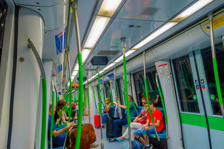 barajas: MADRID, SPAIN - 8 AUGUST, 2015: Inside subway train wagon leaving from Barajas Airport station with some people sitting around. Editorial