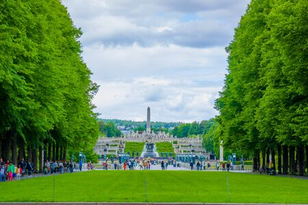 obelisk stone: OSLO, NORWAY - 8 JULY, 2015: The famous monument Monolitten seen from distance sorrounded by other sculptures and green vegetation in Vigelandsparken.